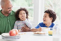 Father having a laugh with sons during breakfast (thumbnail)