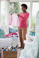 Mid_adult woman folding laundry in sunroom