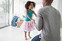 Young girl in tutu dancing with her dad