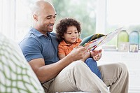 Father reading to young son in sunroom