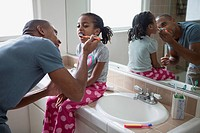 Dad brushing young daughter's teeth