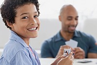 Preteen boy playing cards with his dad.