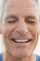 Portrait of senior man smiling with eyes closed