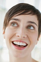 Close_up of smiling young adult woman looking up