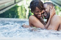 Couple holding each other and laughing in hot tub