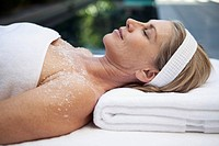 Middle_aged woman having salt scrub treatment