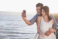 Couple taking picture by waterfront