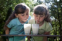 Twins in garden, drinking milk