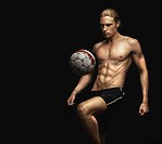 A handsome young shirtless man bouncing a soccer ball on his knee