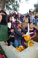The cemetery is the heart of the Day of the Dead in Santiago Sacatepequez celebration with many families and widows sitting beside the graves of their...