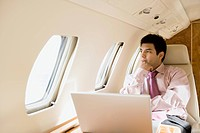 Businessman with laptop computer on jet airplane