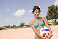 Woman holding volley ball on beach