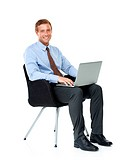 An amiable businessman working on his laptop while sitting in an office chair