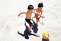 Boys Dribbling Ball on Beach