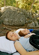 Young couple lying in sleeping bags outside