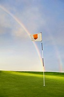 Rainbow falling onto putting green and golf pin, summer, daytime