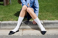 Gawky Girl Wearing Pointy Shoes Sitting on Curb