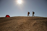 Two Hikers Walking Towards Tent