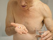 An elderly man taking medication