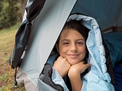Girl covered in sleeping bag looking out of tent