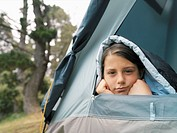 Girl covered with a sleeping bag looking out of a tent