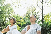 Couple meditating outdoors