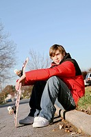 Boy sitting on a curb with his skateboard