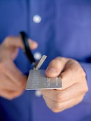 Man cutting up credit card with scissors