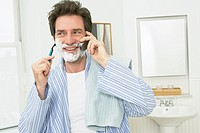 Man talking on the phone while he shaves