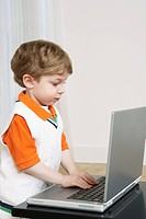 Young boy plays with a laptop computer