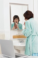 Woman checking her email while brushing her teeth