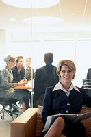 Businesswoman sitting in waiting area with conference room behind