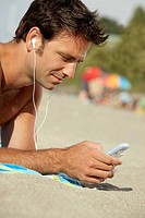 Man using an MP3 player on the beach