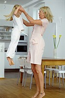 Mother and daughter in kitchen, girl jumping in mid_air