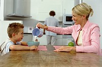Mother and son sitting at table in kitchen, mother pouring milk in bowl
