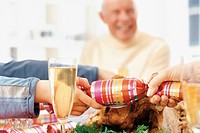 Hands Pulling Christmas Party Favor at Dinner Table
