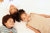 Children lying down with heads together