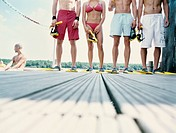 Group of young people standing on jetty with diving goggles and flippers
