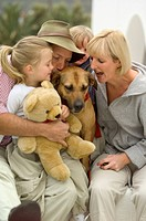 Family of four with dog and teddy bear