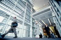 Blurred view of people walking down a hall in an airport setting