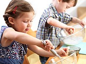MODEL RELEASED. Young children baking. Three year old twins baking.
