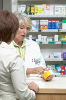 View of female pharmacist talking to woman while holding yellow and white box