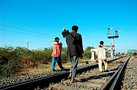 Workers walking in Meterguage railway tracks and signal , Gujarat , India