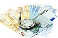 Euro banknotes and antique clock