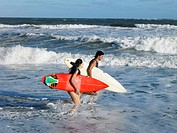 Couple with Surfboards in Sea