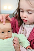 Little girl putting a plaster on her baby doll´s forehead
