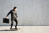 Blurred Businessman Riding a Skateboard