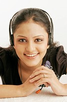Maharashtrian teenage girl happily engrossed in listening to music using earphones MR686M