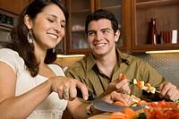 Couple preparing shish kebabs