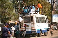 Passengers climbing top of bus used means of local transport to reach their destination in Jharkhand ; India